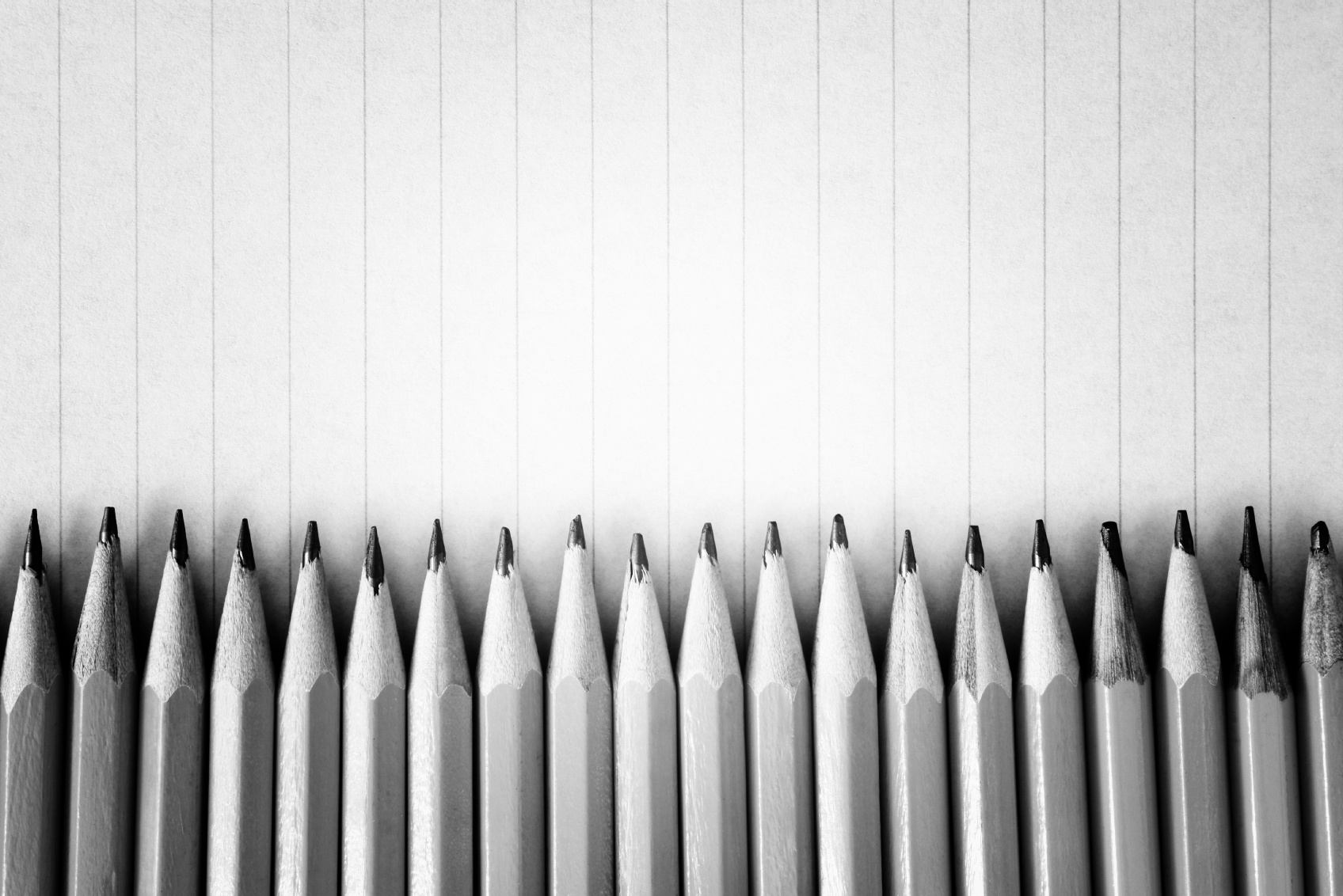 Sharpened pencils on a lined paper background