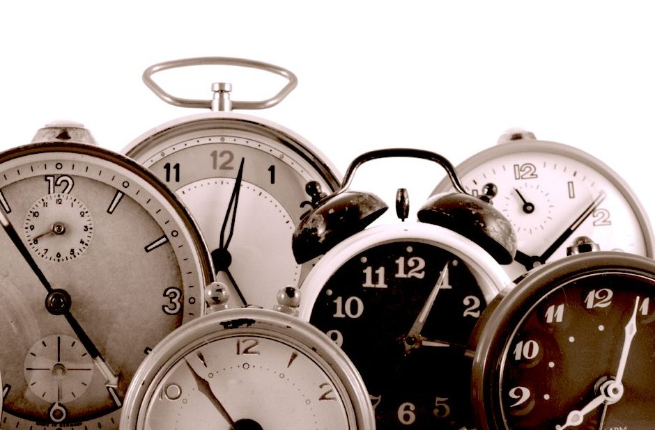 Analogue clocks set to different times on a white background