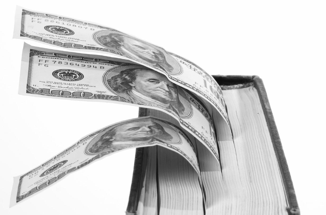 Three dollar bills tucked into the top of a hardback book