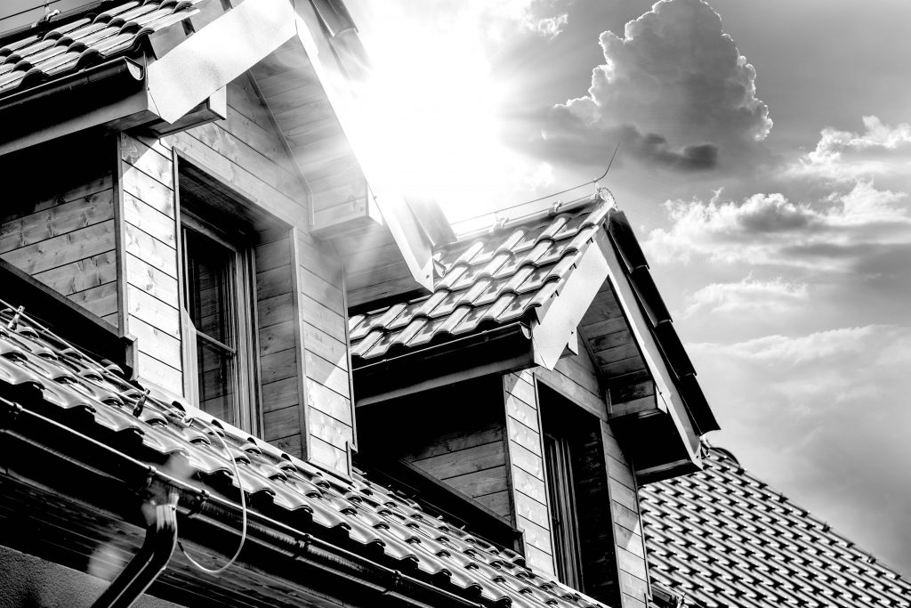A house roof with two dormer windows and the sun shining between them