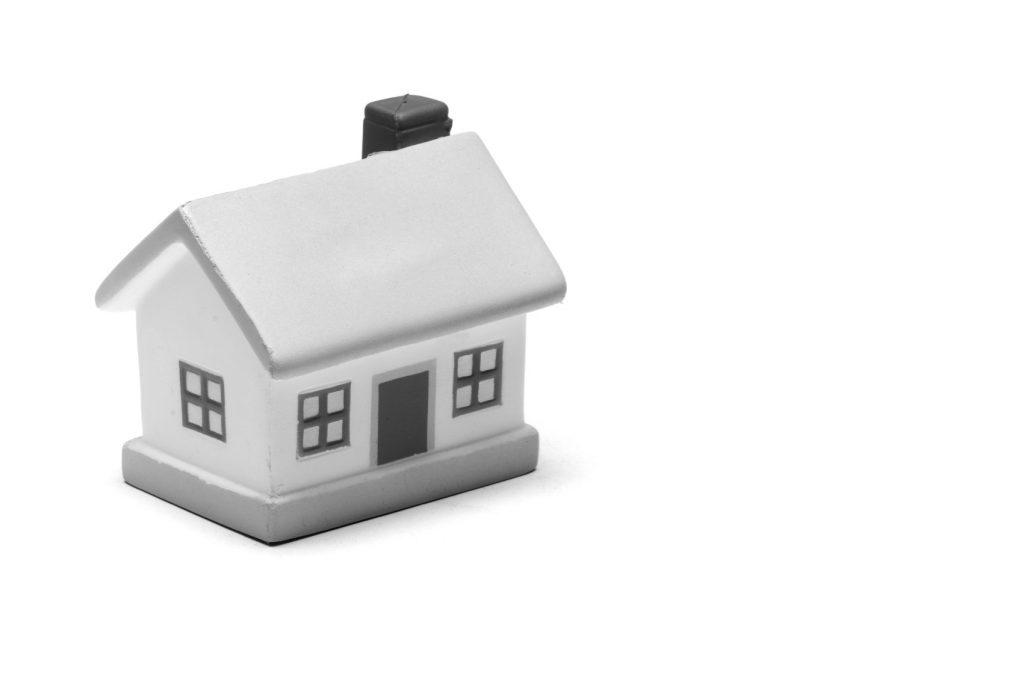 Miniature toy house on plain white background