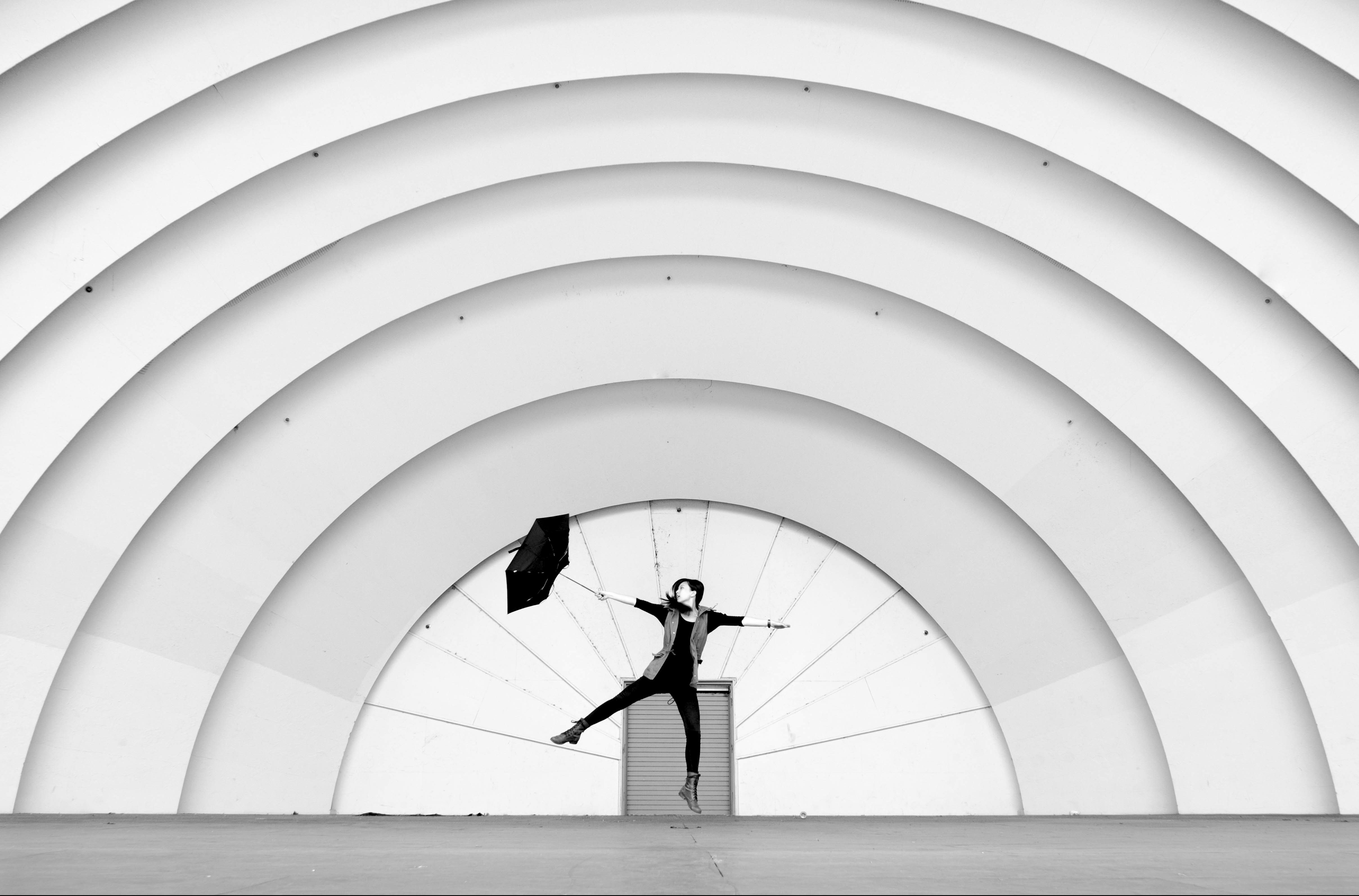Person with umbrella jumping in front of a building