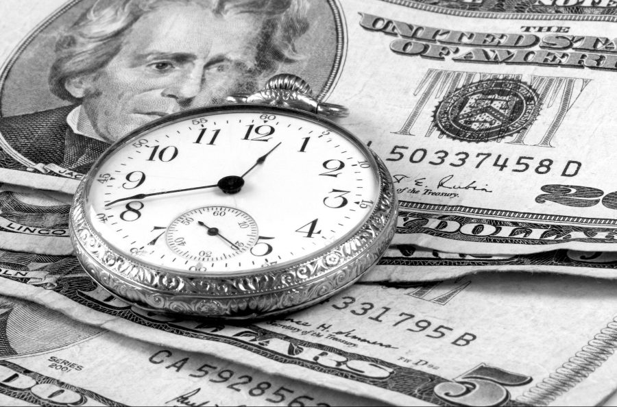 Pocket watch on pile of dollars