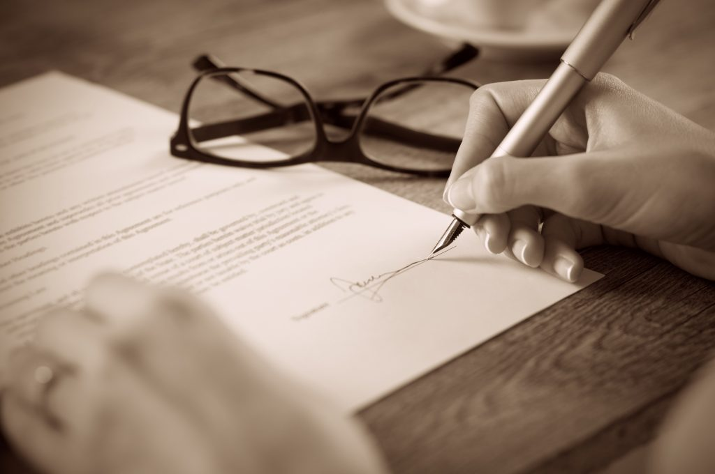 Close up of person signing a contract