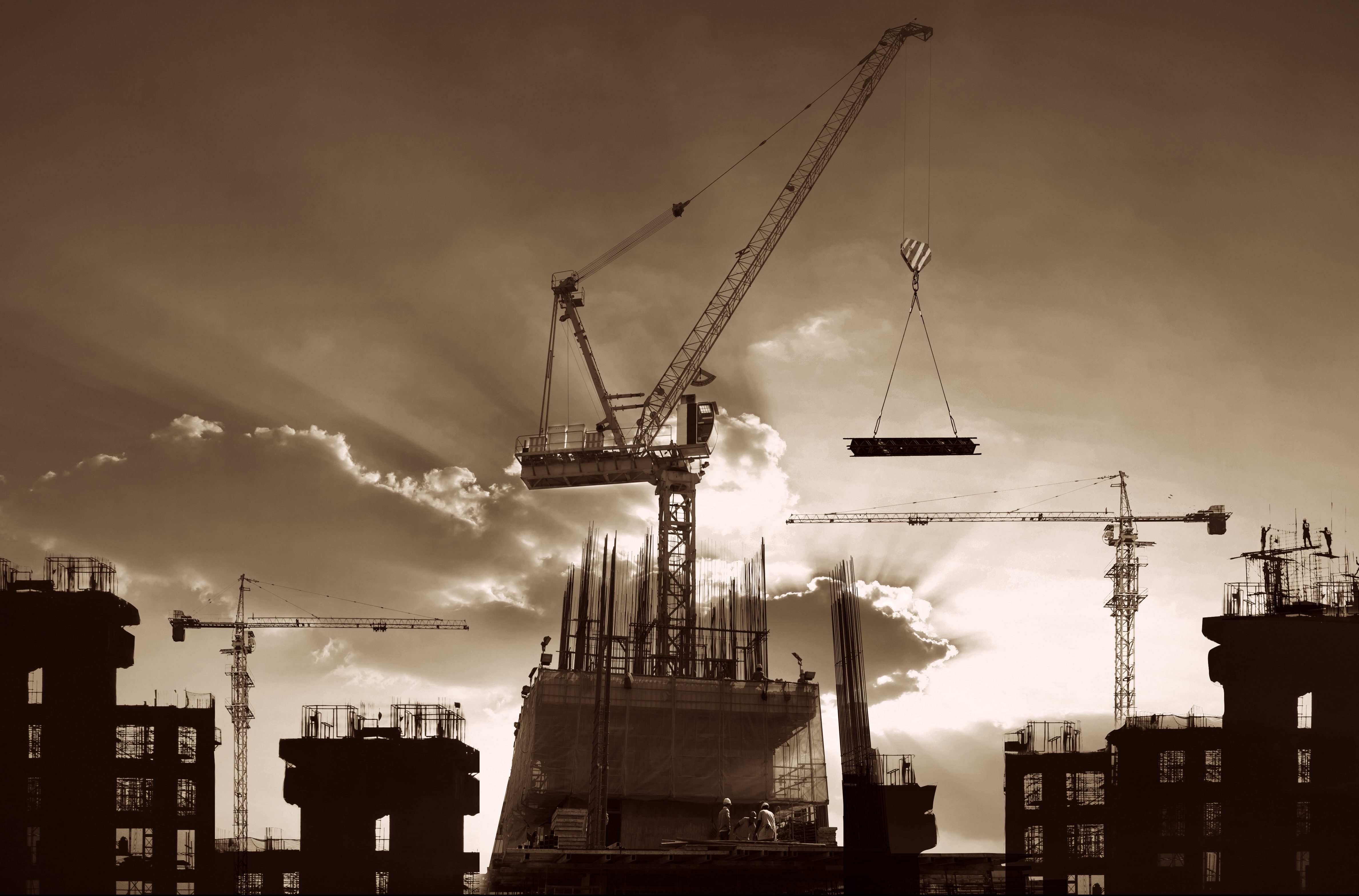Cranes and buildings in construction silhouetted against sunset