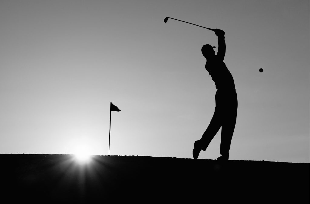 Golfer, flag and golf ball in silhouette against sunset