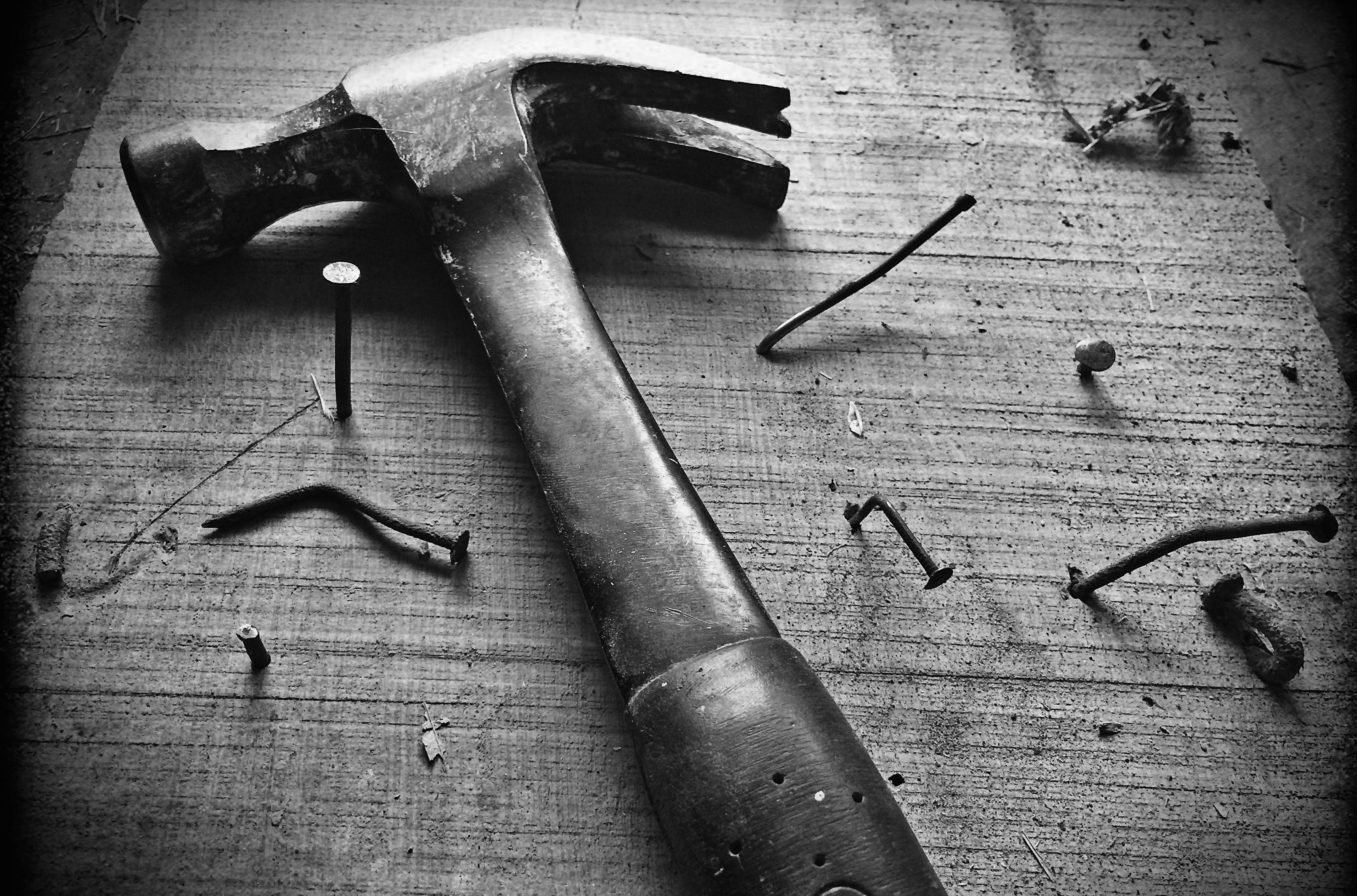 Hammer lying on wooden board with several bent nails in