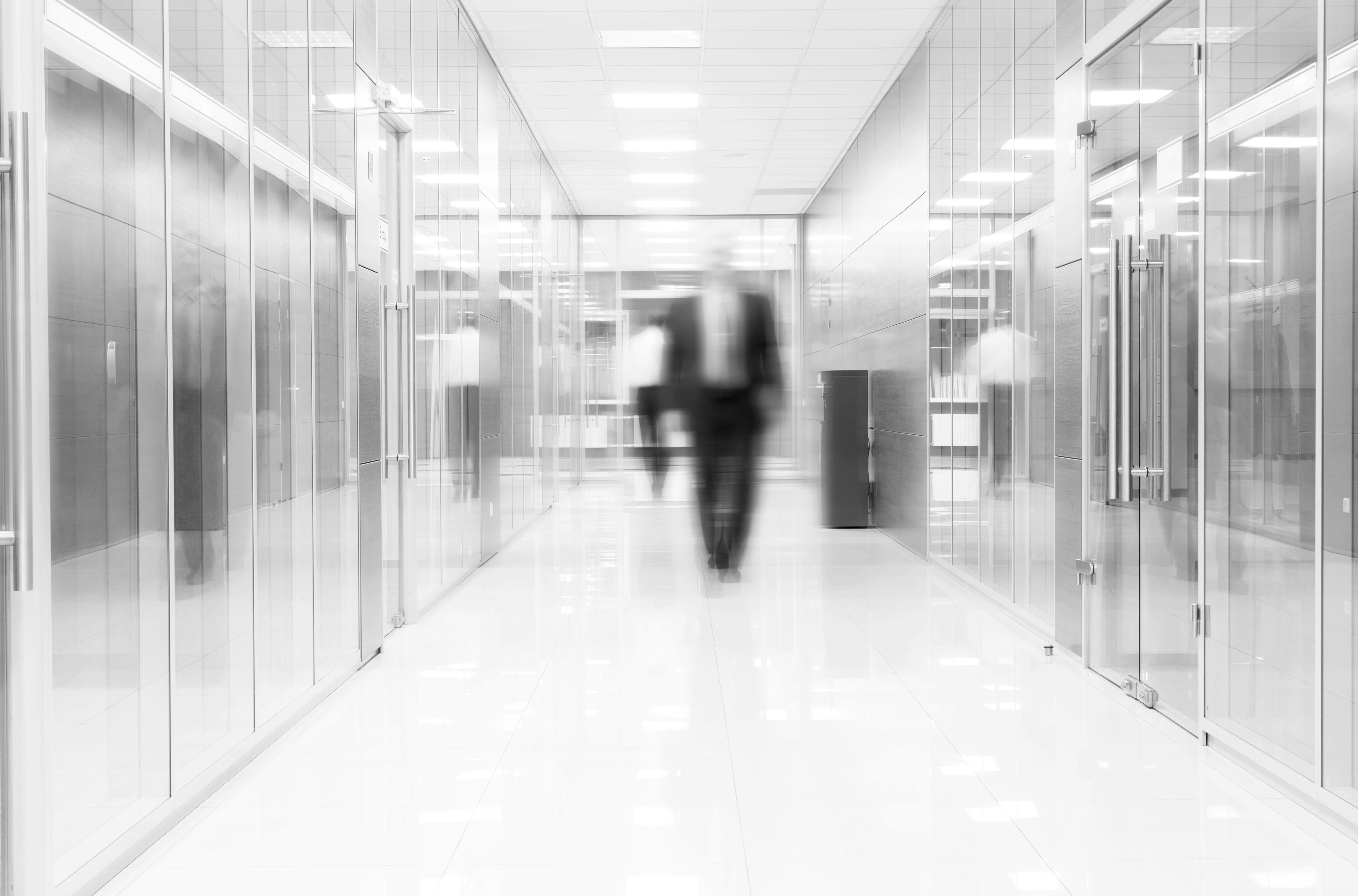 Businessman goes along a corridor at modern office