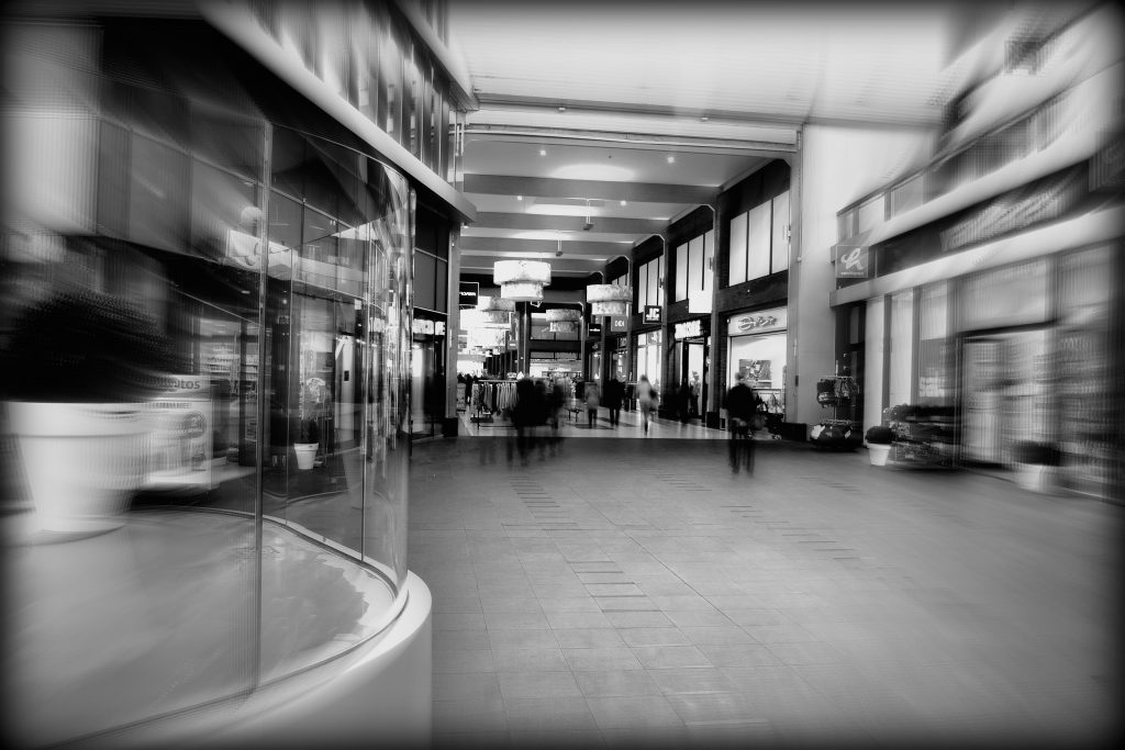 Shopping centre with glass shop front in foreground